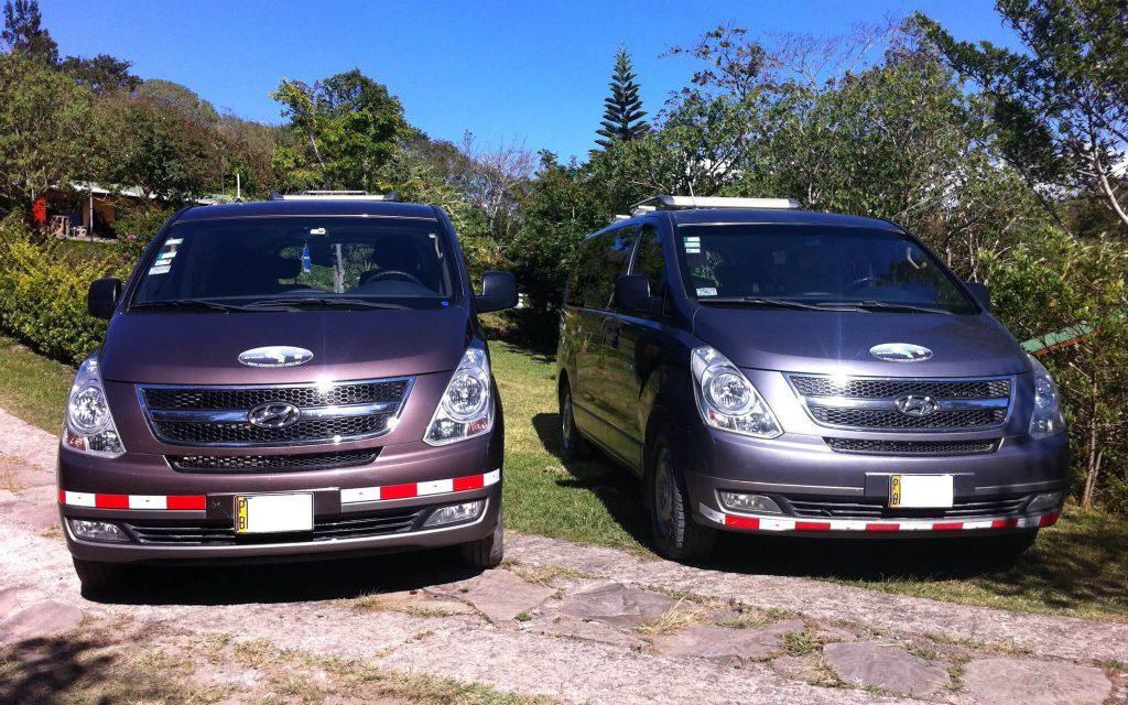 Dos vehículos tipo Van uno a la par del otro.